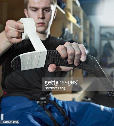 Ice hockey player taping hockey stick