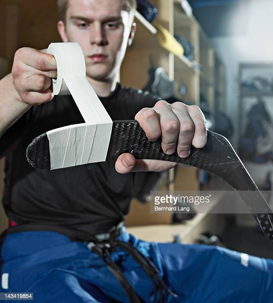 Ice hockey player taping hockey stick