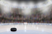 Low angle view of ice hockey puck on ice with deliberate shallow depth of field on brightly lit stadium background and copy space. Fictitious arena created entirely in Photoshop.