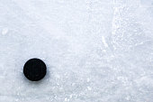Ice hockey rink with a hockey puck with lot of copy space.