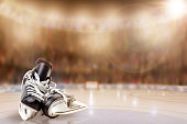 Low angle view of hockey skates on ice with deliberate shallow depth of field on brightly lit stadium background and copy space. Fictitious background arena created in Photoshop.