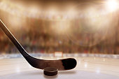 Low angle view of hockey stick and puck on ice with deliberate shallow depth of field on brightly lit stadium background and copy space.  Fictitious stadium was created entirely in Photoshop.
