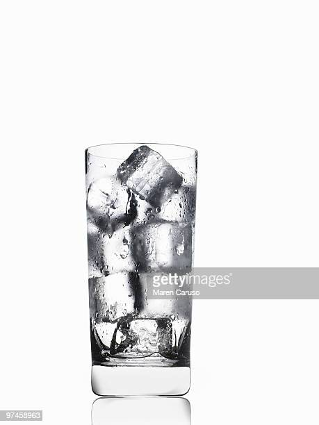 Ice in a tall water glass on white.