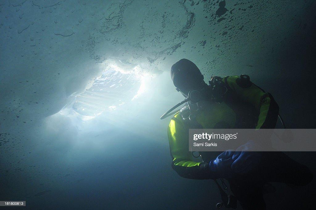 Ice scuba diver with sunbeams through ice hole