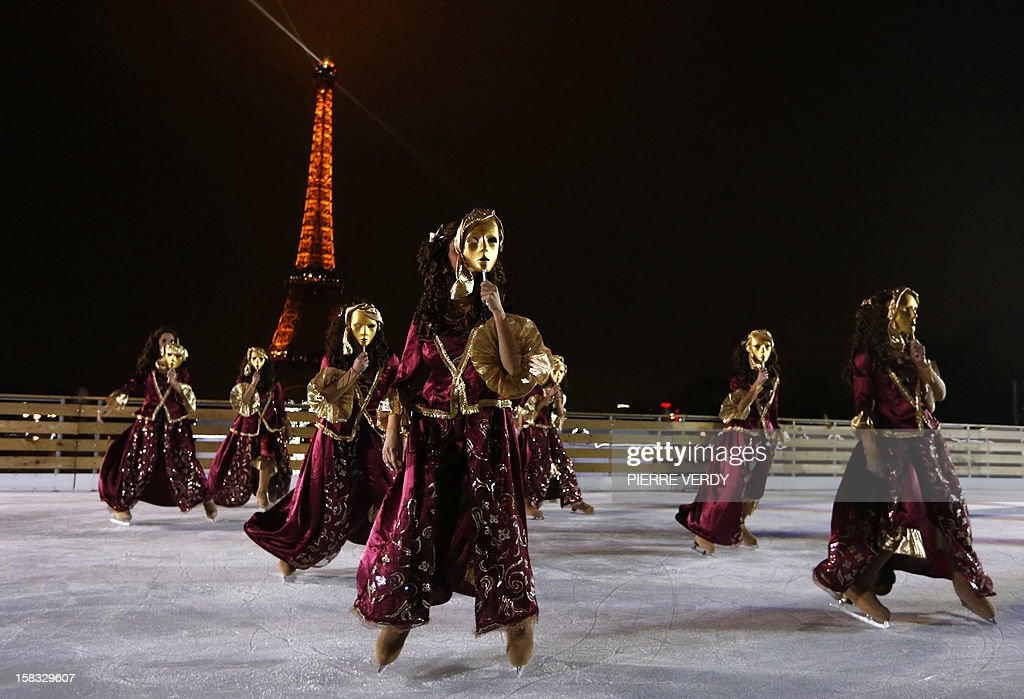 Ice skaters perform dances during the inauguration of the 'Christmas village', on December 13, 2012, in Paris, as part of the 'Trocadero On Ice' event. An ice-skating rink opened to public in front of the Eiffel tower, and will run until January 6, 2013. AFP PHOTO PIERRE VERDY