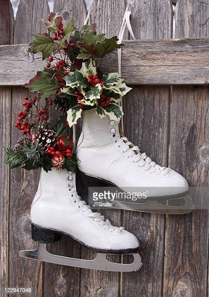 Ice Skates Hanging on Fence with Holly