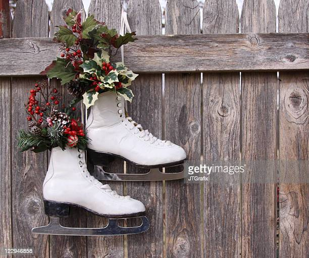 Ice Skates Hanging on Wood Fence with Christmas Holly