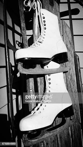 Ice Skates Hanging On Wooden Plank