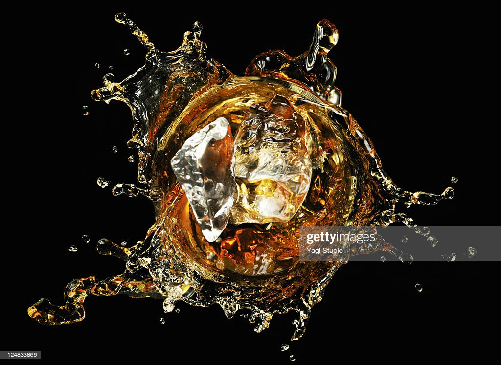 Ice  splashing into whiskey, close-up. : Stock Photo
