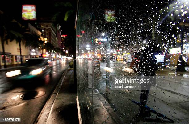 Ice sticks to a window at a bus stop after a winter storm while a woman waits at her stop on Canal Street January 28 2014 in New Orleans Louisiana...