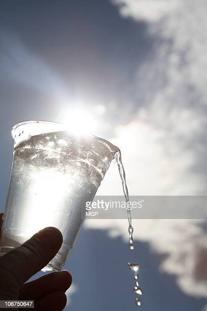 Ice water in plastic cup against sun