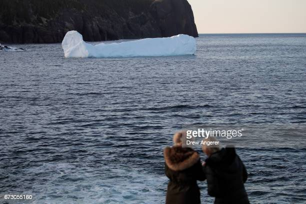 Icebergs float in Flatrock Cove at sunset April 25 2017 in Flatrock Newfoundland Canada Icebergs break off from Baffin Island and Greenland every...