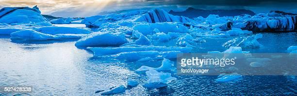 Icebergs floating blue ocean lagoon beneath dramatic Arctic skies Iceland