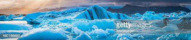 Icebergs floating in tranquil blue waters at sunset panorama Iceland