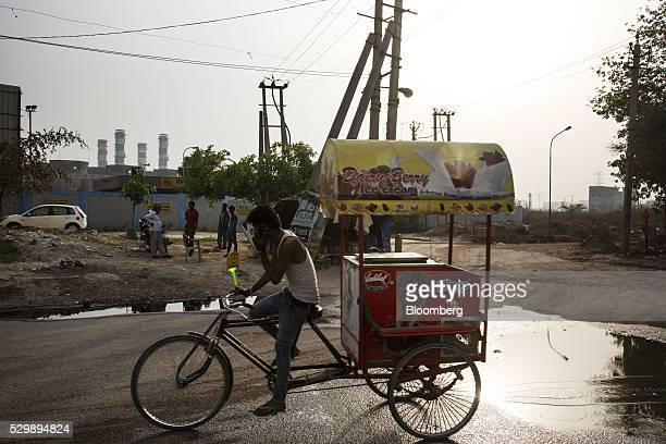 A icecream vendor rides a tricycle past the 1500 Megawatt Combined Cycle Power Station Bawana operated by Pragati Power Corp in Bawana Delhi India on...