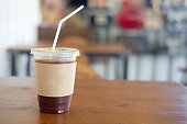 Iced black coffee with brown paper sleeve on wood table