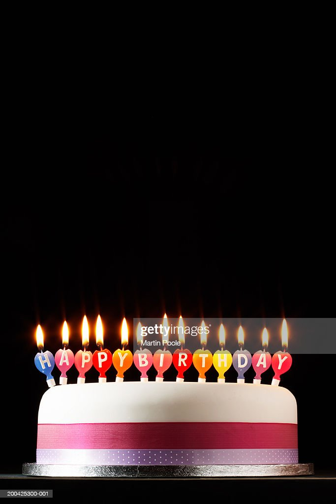 Iced cake lit with happy birthday candles : Stock Photo