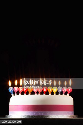 Iced cake lit with happy birthday candles : Bildbanksbilder