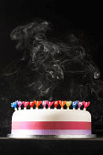 Iced cake with smoking melted happy birthday candles