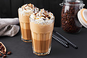 Iced caramel latte coffee in a tall glass with chocolate syrup and whipped cream. Dark background.