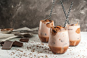 Summer refreshment drinks. Chilled iced chocolate cocoa. With scoop of chocolate ice cream, chocolate powder and ice. In glasses, with tubes for drinking. White concrete table. Copy space