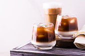 Iced coffee in glasses with milk and cream. White background, wooden table. Horizontal view. Copy space