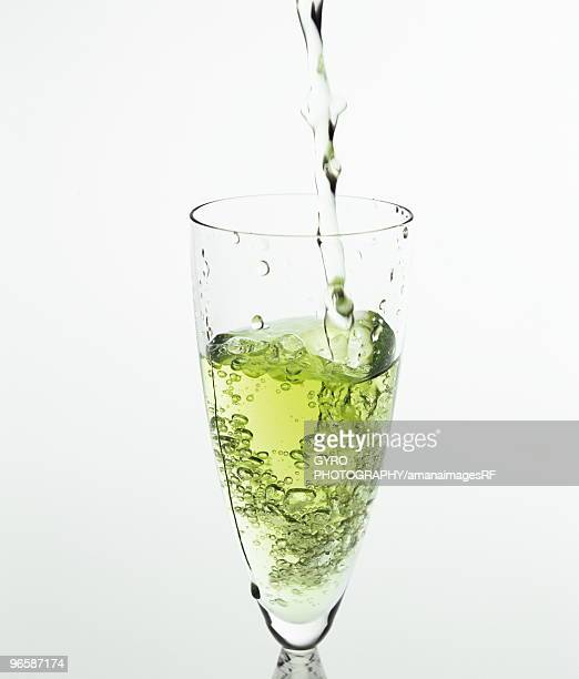 Iced green tea being poured into a glass