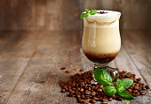 Iced mint  latte in a glass on a rustic wooden background.