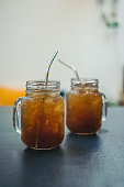 Iced tea in glass mason jars on wooden background, selective focus
