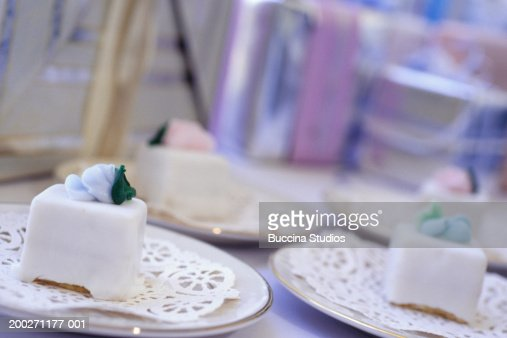 Iced wedding cakes on plates at wedding reception, close-up : Stock Photo