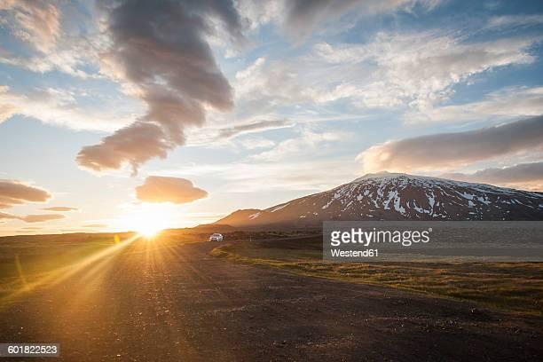 Iceland, car on gravel road under midnight sun