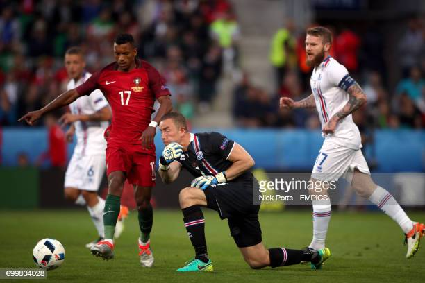 Iceland goalkeeper Hannes Thor Halldorsson rolls the ball out as Portugal's Nani attempts to block