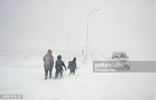 Iceland, Isafjordur, children with adult walking along road in blizzard