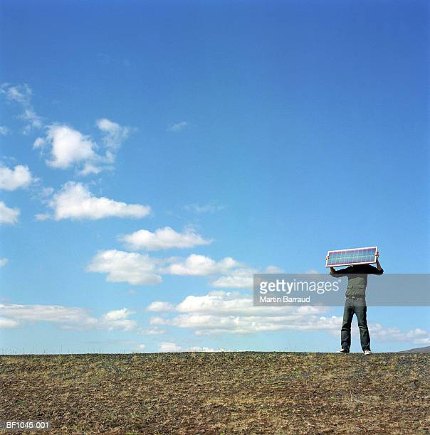 Iceland, Kaldidalur, man holding up solar panel over face