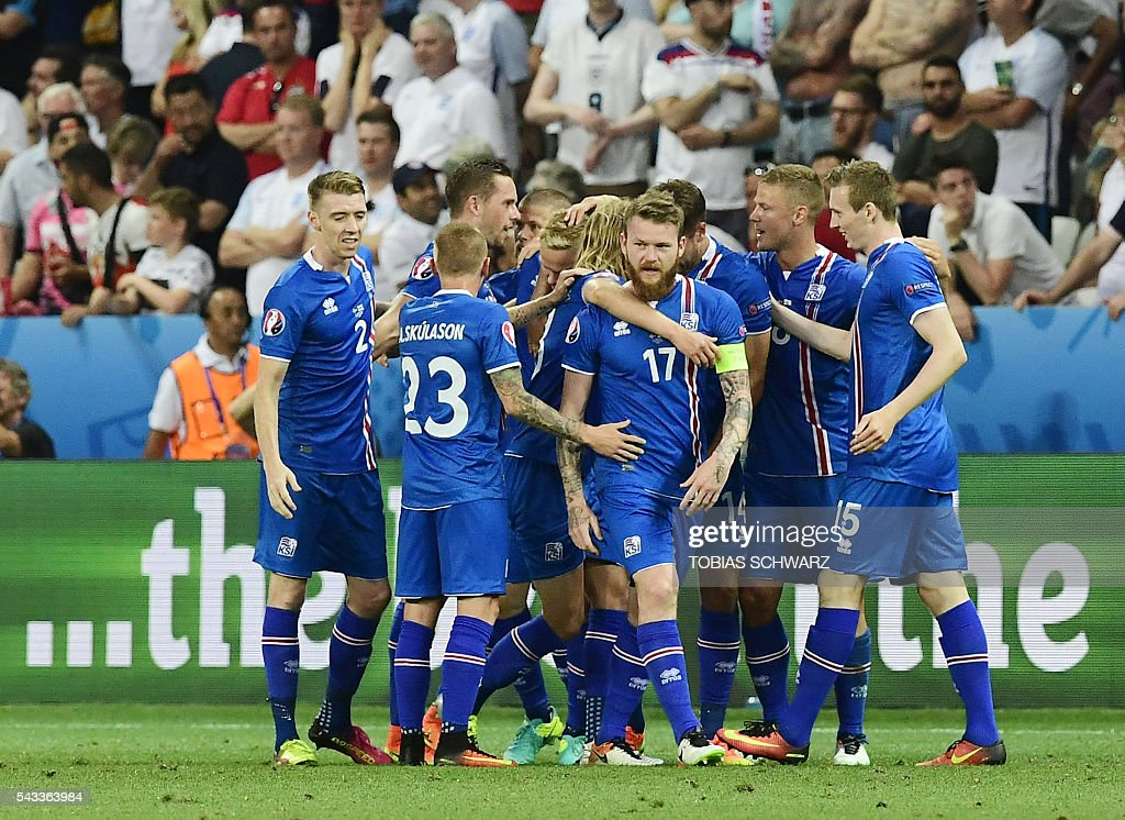 Iceland players celebrate during Euro 2016 round of 16 football match between England and Iceland at the Allianz Riviera stadium in Nice on June 27, 2016. / AFP / TOBIAS