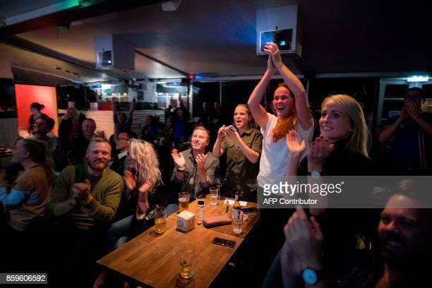 Icelandic football fans react while watching TV their national football team play during the FIFA World Cup 2018 qualification football match against...