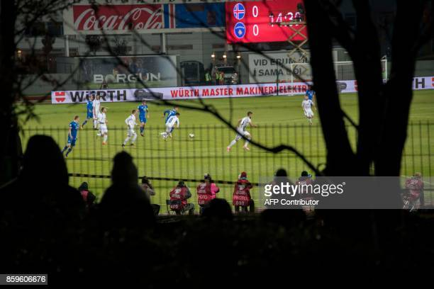 Icelandic football fans who missed out on tickets climb trees and watch between gaps in the fence their national football team play during the FIFA...