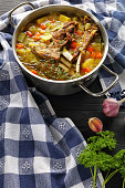 delicious Icelandic Lamb winter hot Soup with vegetables and spices or kjotsupa in a stainless steel casserole pan on wooden table with kitchen towel, classic recipe, vertical view from above