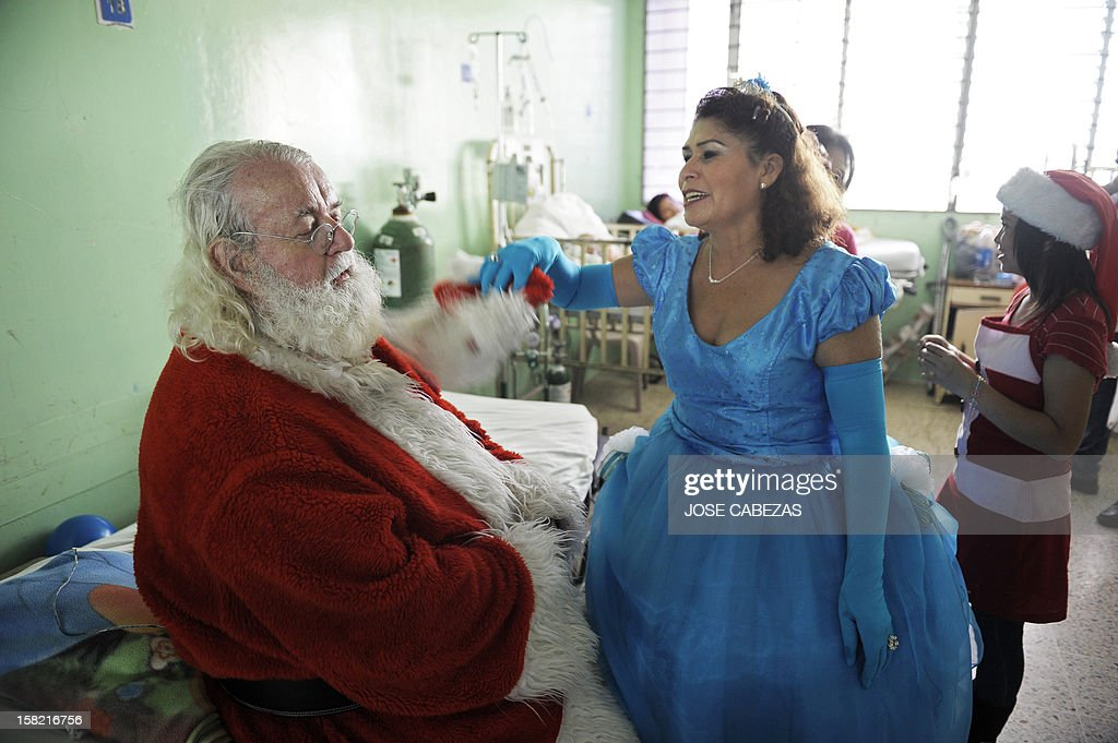 Icelandic philantropist Einar Sveinsson, dressed as Santa Claus, is refreshed by an assistant during a visit to the Benjamin Bloom National Children Hospital, in San Salvador, on December 11, 2012. Sveinsson visits the hospital prior to Christmas every year since 2001 to give gifts to the patients. AFP PHOTO/ Jose CABEZAS