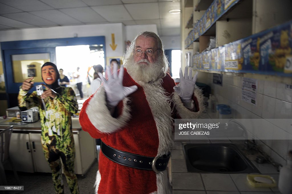 Icelandic philantropist Einar Sveinsson, dressed as Santa Claus, shows his clean hands during a visit to the Benjamin Bloom National Children Hospital, in San Salvador, on December 11, 2012. Sveinsson visits the hospital prior to Christmas every year since 2001 to give gifts to the patients. AFP PHOTO/ Jose CABEZAS