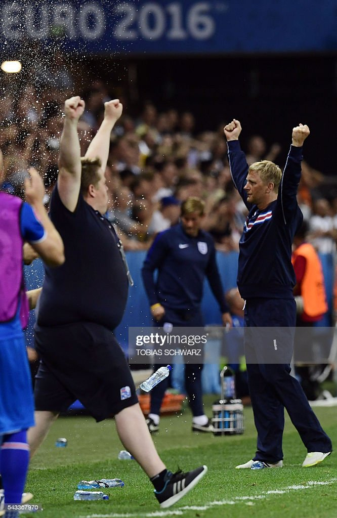 Iceland's coach Heimir Hallgrimsson (R) acknowledges the crowd as the team celebrates their 2-1 win over England in the Euro 2016 round of 16 football match between England and Iceland at the Allianz Riviera stadium in Nice on June 27, 2016. / AFP / TOBIAS