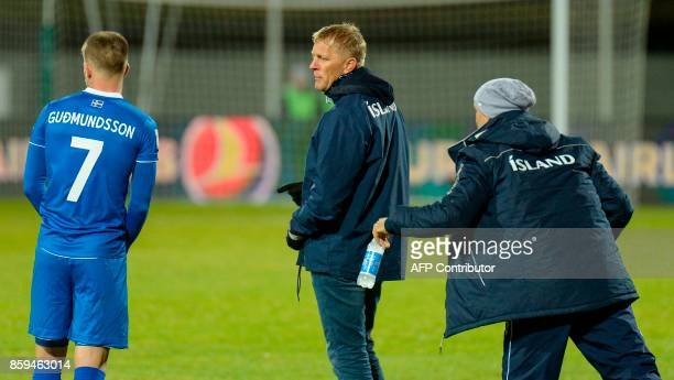 Iceland's coach Heimir Hallgrimsson stands speaks with Iceland's forward Johann Berg Gudmundsson on the sidelines during the FIFA World Cup 2018...