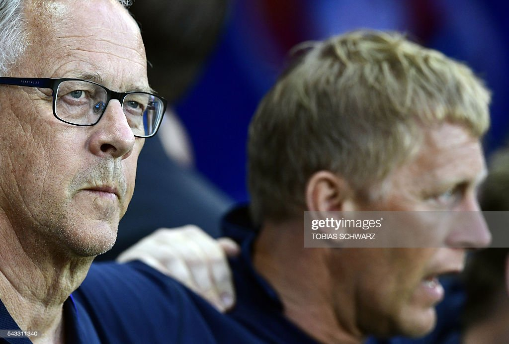 Iceland's coach Lars Lagerbaeck (L) and Iceland's coach Heimir Hallgrimsson stand on the pitch during the singing of the national anthems at the start of the Euro 2016 round of 16 football match between England and Iceland at the Allianz Riviera stadium in Nice on June 27, 2016. / AFP / TOBIAS
