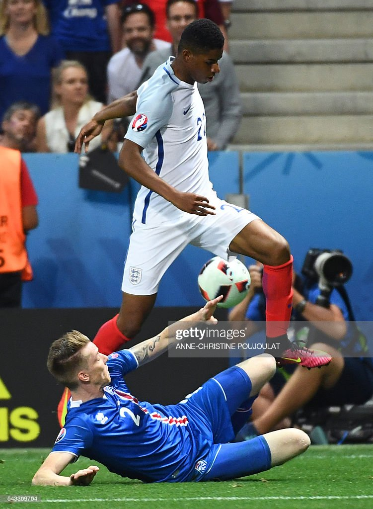 Iceland's defender Birkir Saevarsson and England's forward Marcus Rashford (top) vie for the ball during the Euro 2016 round of 16 football match between England and Iceland at the Allianz Riviera stadium in Nice on June 27, 2016. / AFP / ANNE