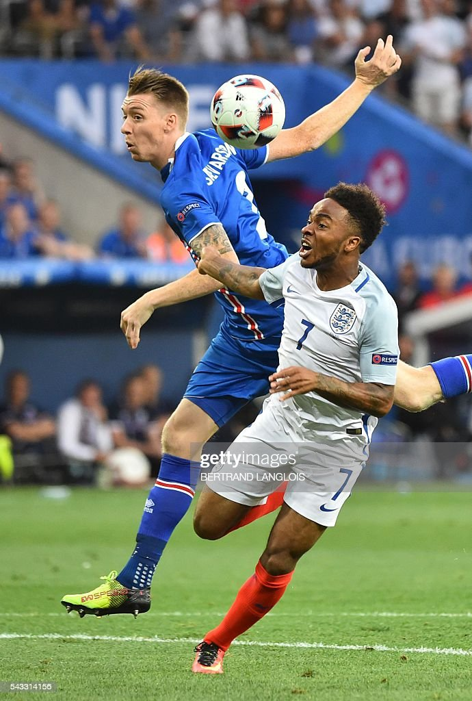 Iceland's defender Birkir Saevarsson (L) and England's midfielder Raheem Sterling vie for the ball during the Euro 2016 round of 16 football match between England and Iceland at the Allianz Riviera stadium in Nice on June 27, 2016. / AFP / BERTRAND
