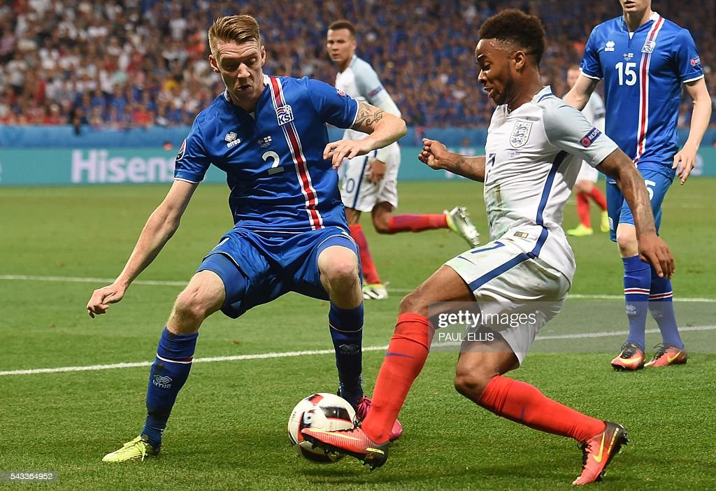 Iceland's defender Birkir Saevarsson (L) vies for the ball against England's midfielder Raheem Sterling during Euro 2016 round of 16 football match between England and Iceland at the Allianz Riviera stadium in Nice on June 27, 2016. / AFP / PAUL