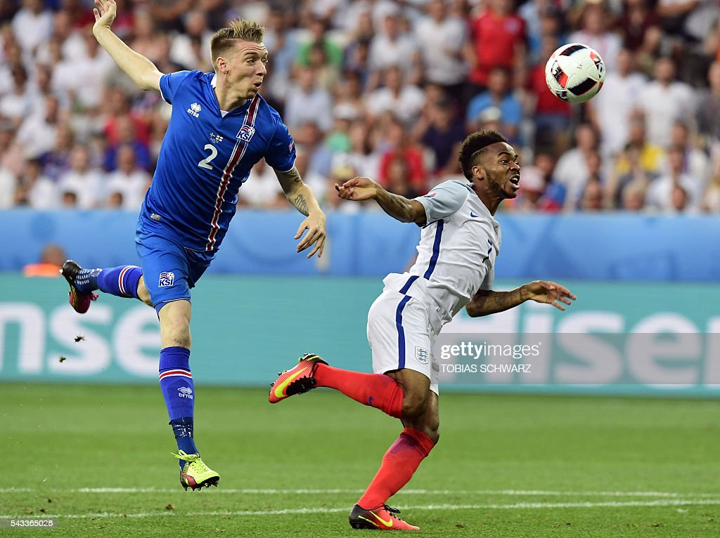 Iceland's defender Birkir Saevarsson (L) vies for the ball against England's midfielder Raheem Sterling during Euro 2016 round of 16 football match between England and Iceland at the Allianz Riviera stadium in Nice on June 27, 2016. / AFP / TOBIAS