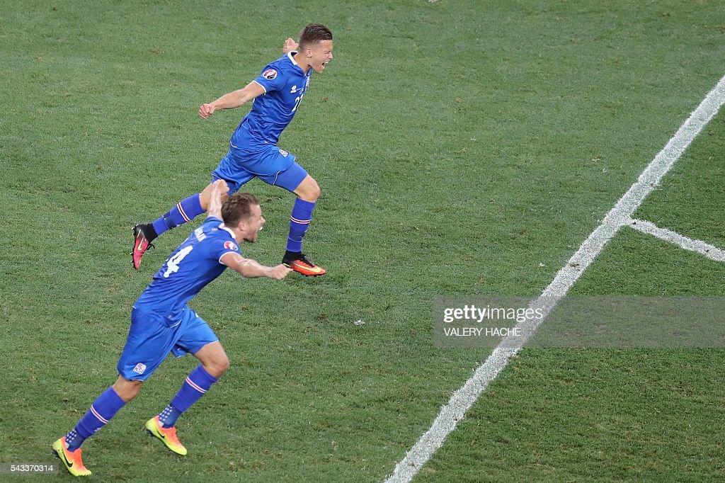 Iceland's defender Kari Arnason and Iceland's midfielder Arnor Ingvi Traustason celebrate their team's win after the Euro 2016 round of 16 football match between England and Iceland at the Allianz Riviera stadium in Nice on June 27, 2016. Iceland won the match 1-2. / AFP / Valery HACHE