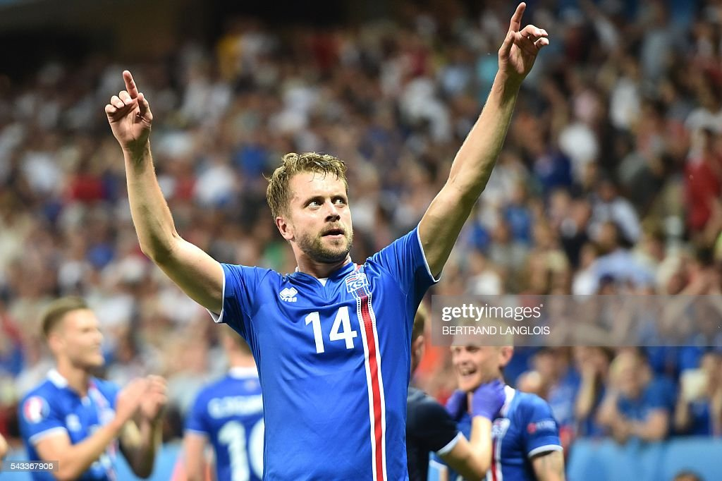 Iceland's defender Kari Arnason celebrates his team's win after the Euro 2016 round of 16 football match between England and Iceland at the Allianz Riviera stadium in Nice on June 27, 2016. Iceland won the match 1-2. / AFP / BERTRAND