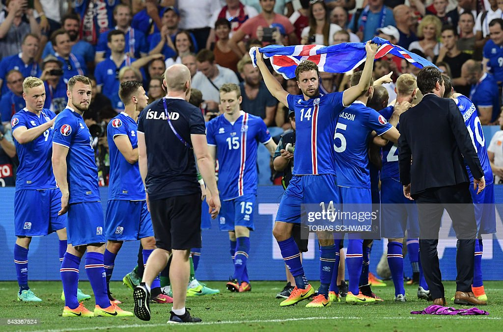 Iceland's defender Kari Arnason holds up the national flag as the team celebrate their 2-1 win over England during Euro 2016 round of 16 football match between England and Iceland at the Allianz Riviera stadium in Nice on June 27, 2016. / AFP / TOBIAS